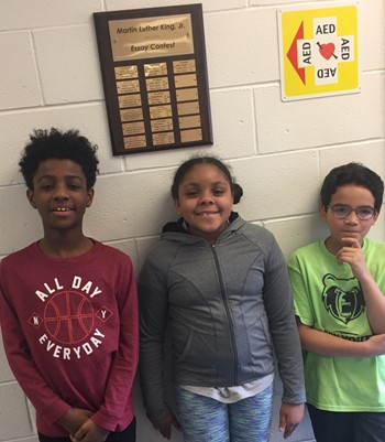 3 students standing in front of a plaque