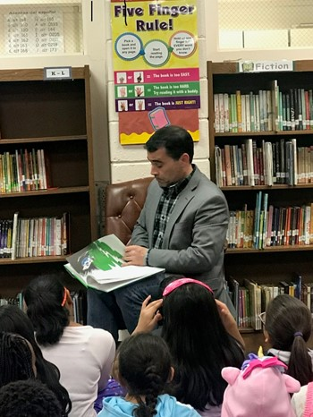 Man reading a book to children