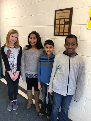 Four Students Standing By a Plaque