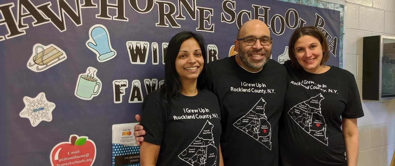 Three Teachers Standing In Front of a Bulletin Board