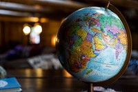Globe with soft lighting in a darker, unfocused background.